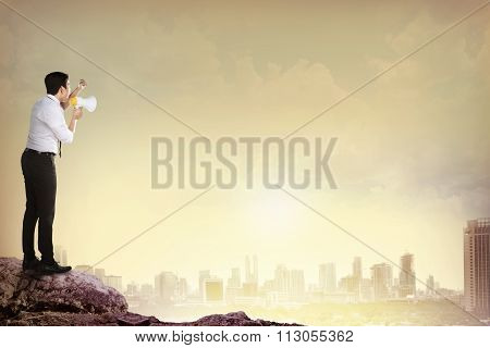 Man Standing On The Top Of Mountain, Yelling Using Megaphone