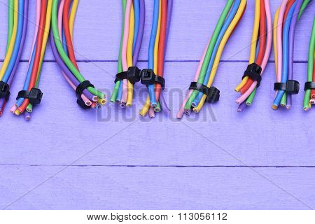 Colored cables in groups on the wooden background
