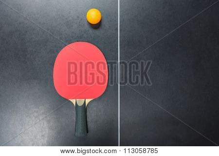Table Tennis Racket With Orange Ball On Table
