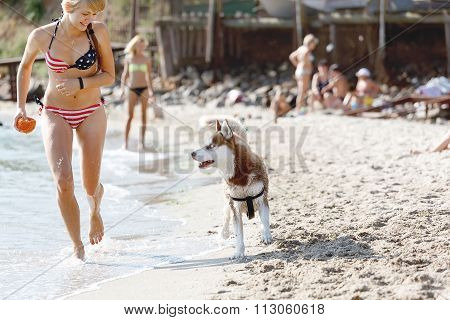 Young girl running on the beach with dog