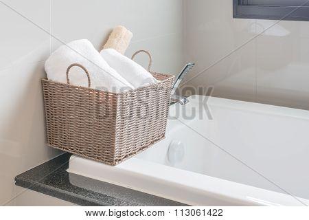 White Towel In Basket On Bath Tub