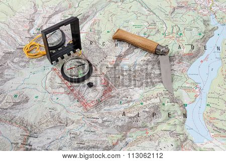 Compass and wooden-handled knife on a hiking map of the Berchtesgaden Alps