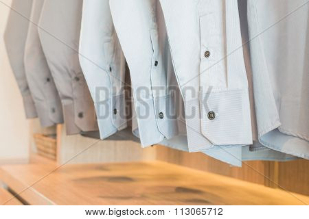 Shirts Hanging On Rack In Wooden Wardrobe