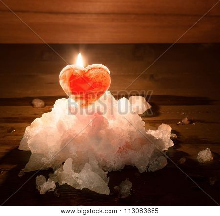 Red Ice Heart And The Burning Candle Behind It On A Hill Of White Snow