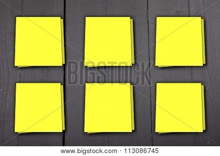 Six Yellow Memo Notes On Dark Black Wooden Background