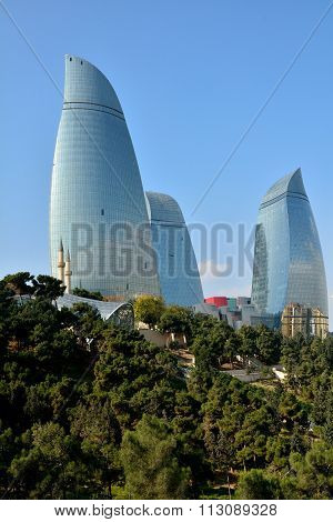 Looking up at the Flame Towers in Baku, capital of Azerbaijan, in the sunshine with trees