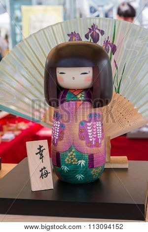 Traditional Japanese Wooden Kokeshi Doll And Wagasa Umbrella In Background
