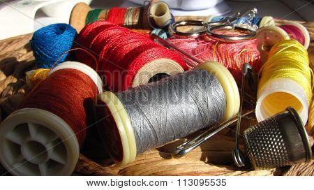 Sewing kit scattered random on wattle board.