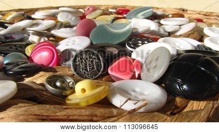 Buttons scattered random on wattle board.