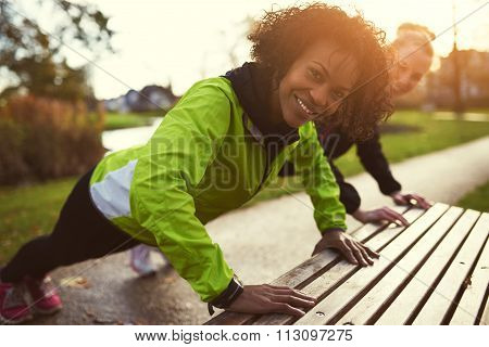 Two Smiling Sportswomen Doing Push-ups