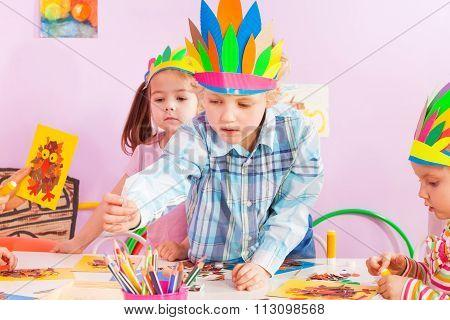 Boy reaching pencil in kindergarten class