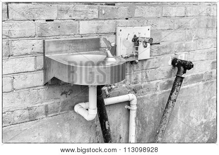 A Photo Of Black And White Angular Water Pipes Connected To  A Stainless Steel Basin On A Beige Bric