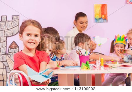 Little girl with mates in origami class