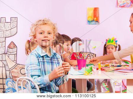 Blond boy in preschool class sit by table