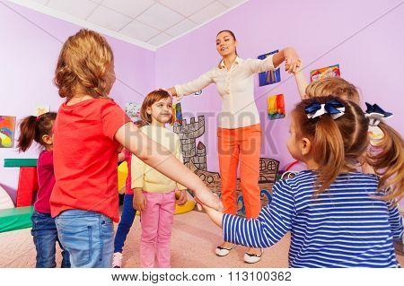 Group of kids play roundelay around girl