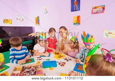 Teacher helps kids glue craft images