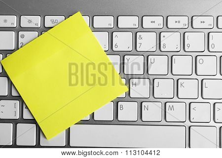 Empty yellow adhesive paper on keyboard, on light background