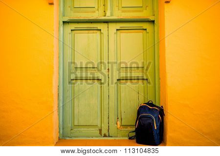 Blue back pack near the green door and yellow wall