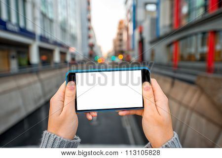Holding Smartphone on the city background