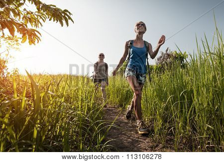Ladies hikers walking through the meadow with lush grass at sunny hot day