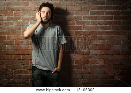 Young handsome man in grey T-shirt listening music with headphones on brick wall background