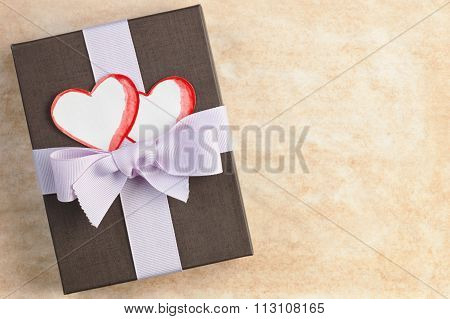 Gift Box Tied By Ribbon With Handmade Paper Hearts Against Stained Paper Background With Space For T