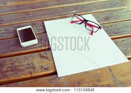 Top View Of Creative Workspace With White Paper Blank And Mobile Phone On Wood Table