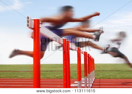 Hurdle race, men jumping over hurdles in a track and field race. Motion blurred image, digitally altered unidentifiable face.