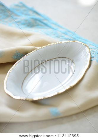 Empty oval shape decorative plate and drapery.