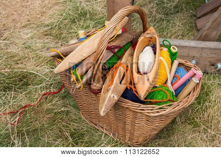 Weaving Shuttles And  Multi-colored Yarn In A Basket
