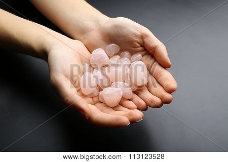 Woman holding semiprecious stones in her hands on dark grey background