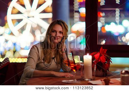 Young woman drining cocktail in restaurant