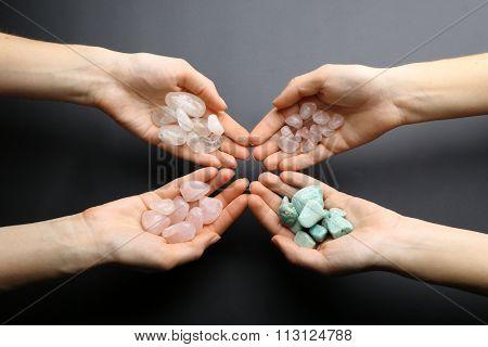 Women holding semiprecious stones in their hands on dark grey background