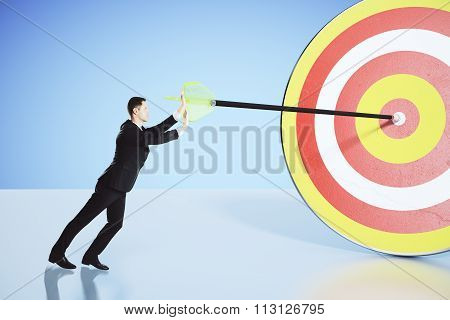 Move Towards Your Goal Concept With Businessman Pushing An Arrow Into The Bullseye
