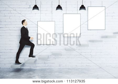 Businessman Climbs Up The Stairs At White Brick Wall With Blank White Posters, Mock Up
