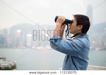 Man looking though binoculars at Hong Kong