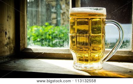 Glass Of Fresh Beer On Old Wooden Window Sill .