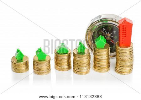 Stacks of coins, green and red home with compass.