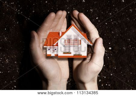 Hands holding house representing home ownership and real estate concept