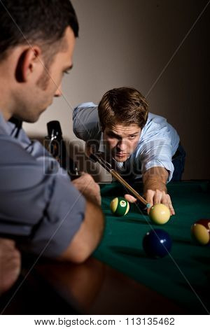 Young casual caucasian man concentrating hard on strike at billiard game with friend. Holding cue ready to strike the ball.