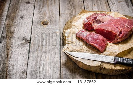 Cutting Raw Meat A Large Knife. On Wooden Table.