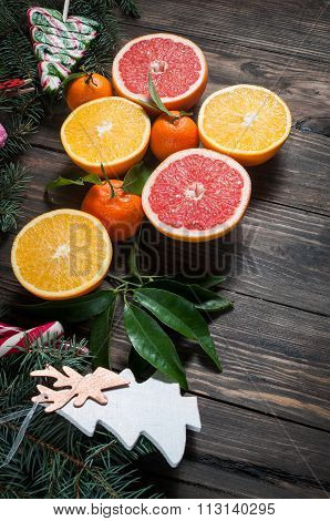 Tangerines with leaves in Christmas decor with Christmas tree, dry orange and candies over old woode
