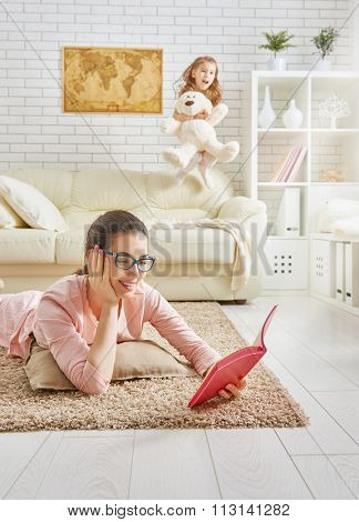 Family relax. Mother reading a book and child jumping on the sofa.