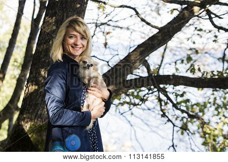 Woman in blue coat with dog smiling