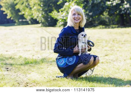 Pretty blonde lady holding her scared chihuahua