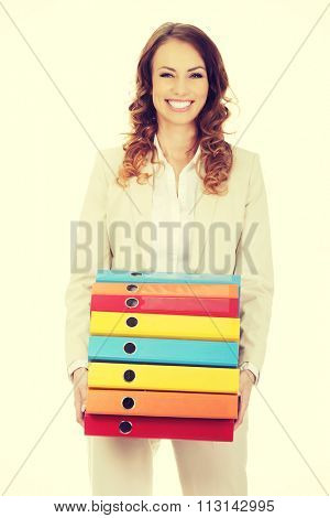 Female office worker carrying heavy binders.