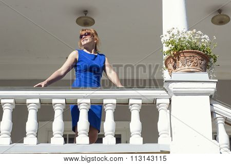 Wealthy beautiful woman standing on the balcony