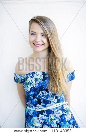 Woman in a blue dress smiles posing