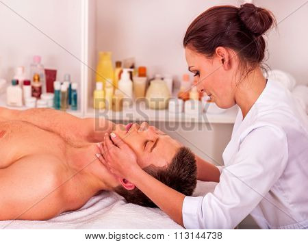 Man getting facial  massage in beauty spa. Two people.
