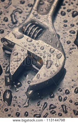 Adjustable spanner in water drops close up